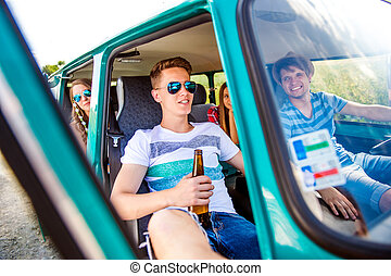 Teenagers inside an old campervan, drinking beer, roadtrip -...