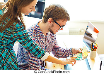 Young man and woman looking to a color paint palette - Young...
