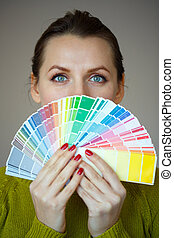 Woman in a glasses looking to a color paint palette -...