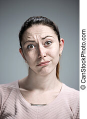 Woman is looking imploring over gray background - Woman...