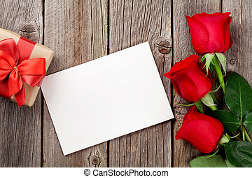 Red roses, greeting card and gift box