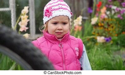 Small girl frowning and confused in the garden in slowmotion...