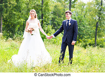 Bride and groom holding hands outdoors