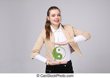 Young woman holding ying yang symbol - Young woman holding...