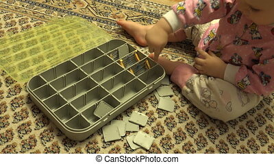 Newborn Baby Playing with Plastic Case with Hardware Items....