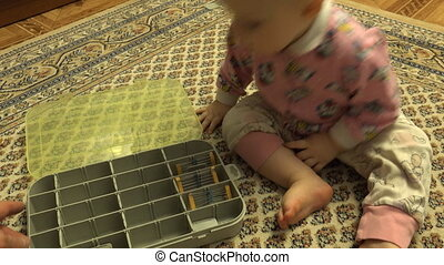 Newborn Baby Playing with Plastic Case with Hardware Items...