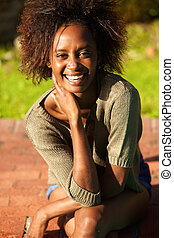 Young black woman smiling outdoors - Portrait of a cheerful...
