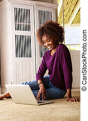 Young black woman sitting on floor with laptop