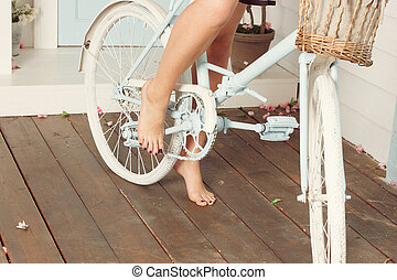Woman bare feet near the blue bicycle in spring