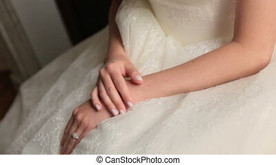 Beautiful brunette bride sits with with folded arms and...