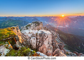 rock with grass on top of tirol mountains at sunset