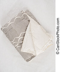 A Folded Gray Duvet with White Concave Line Pattern - A...