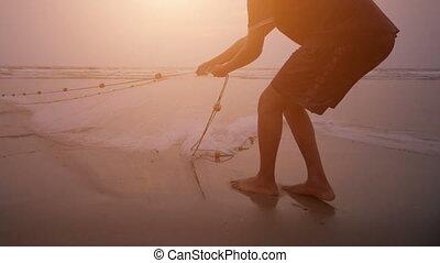 Fishermen pull net from the ocean