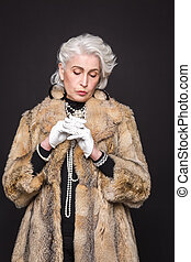 Senior rich woman posing with white gloves on isolated on...