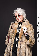 Senior rich woman with blond hair smiling for camera and...