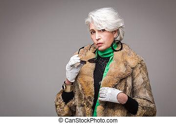 Senior rich woman - Portrait of senior rich woman holding...