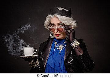 Senior rich woman having a cup of tea as Queen Elizabeth...