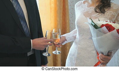 The bride and groom holding glasses of champagne in front of...