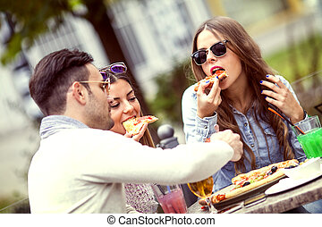 Pizza time - Close-up of three young cheerful people eating...