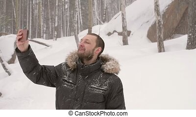 Man taking a selfie in a winter forest under the snow