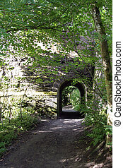 Path and archway through a stone wall near Dunkeld,...