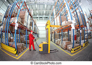 forklift operator in warehouse - worker in red uniform at...