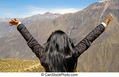 Woman feels free in the mountains, south america