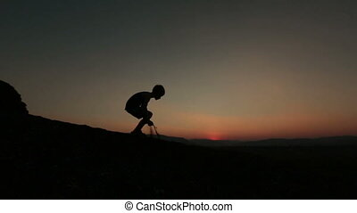 Silhouette of little boy playing with sand on sunset in the mountains
