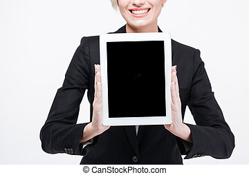 Happy businesswoman showing blank tablet computer screen -...