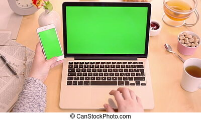 using laptop and phone green screen - Woman using laptop and...