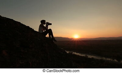 Silhouette of woman-photographer taking photos of sunset in the Alpine mountains