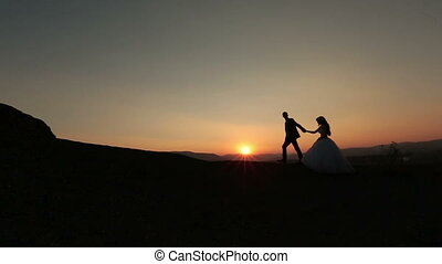 Bride and groom walk and hold hands in the Alpine mountains.