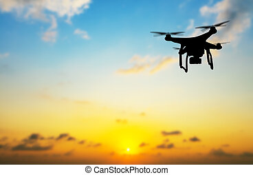 Flying silhouette of drone against sunset - Flying...