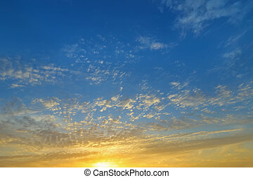 Natural Clouds formation on a blue sky in the evening with yellow shade of the sun