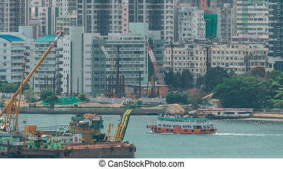 Star Ferries and other ships are sailing through Victoria Harbour timelapse hyperlapse, with the skyline of Hong Kong as backdrop