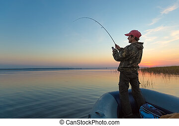 Man fishing on the lake - Man fishing from the boat on the...