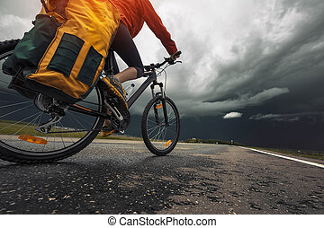 Cycling - Lady hiker riding loaded bicycle on the paved...