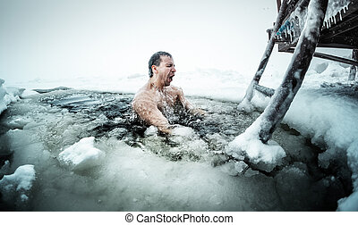Ice hole swimming - Young man swimming in the ice hole on a...