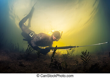Spearfishing - Underwater shot of the man with speargun