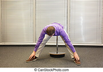 man stretching legs and back sitting on pneumatic stool in...