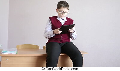 boy playing tablet sitting on the desk in the classroom