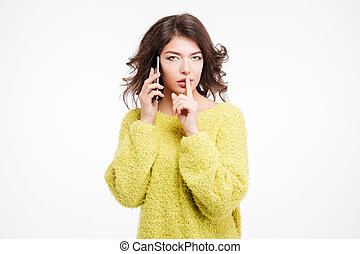 Woman talking on the phone and showing finger over lips...