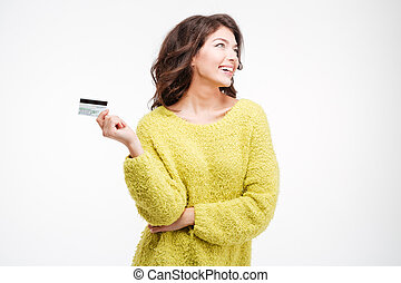 Happy thoughtful woman holding bank card isolated on a white...