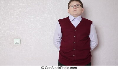 boy with glasses standing against a wall and looking at the...