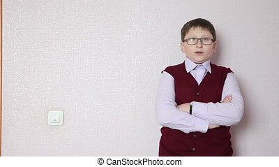 boy with glasses standing against a wall