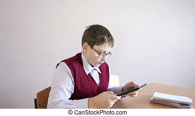 boy with glasses playing the tablet at school HD