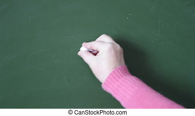 woman draws sun chalk on a blackboard