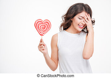 Laughing woman holding lollipop - Portrait of a young...