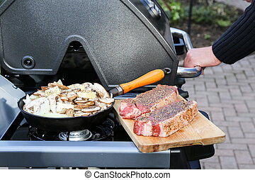 Heating up the BBQ - a hand reaches in to lift the lid to...
