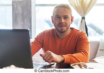 Handsome young man working on notebook, smiling, looking at camera, while enjoying coffee in cafe